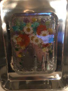 Na zdjęciu znajdują się zatopione w plastiku sztuczne kwiaty oraz zastrzyki z hormonami, które artystka brała zanim zaszła w ciążę.
