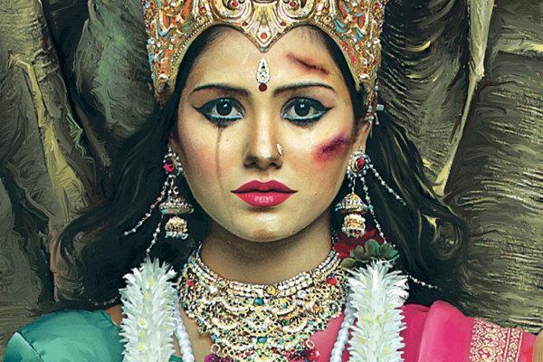 Na obrazku znajduje się kobieta, która utożsamia indyjską boginię Lakszmi z śladami pobicia na twarzy. Po policzku spływa jej łza.