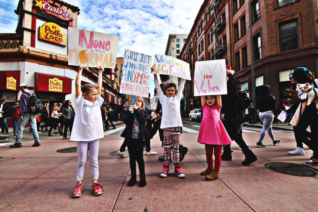 Cztery dziewczynki trzymają transparenty na demonstracji feministycznej