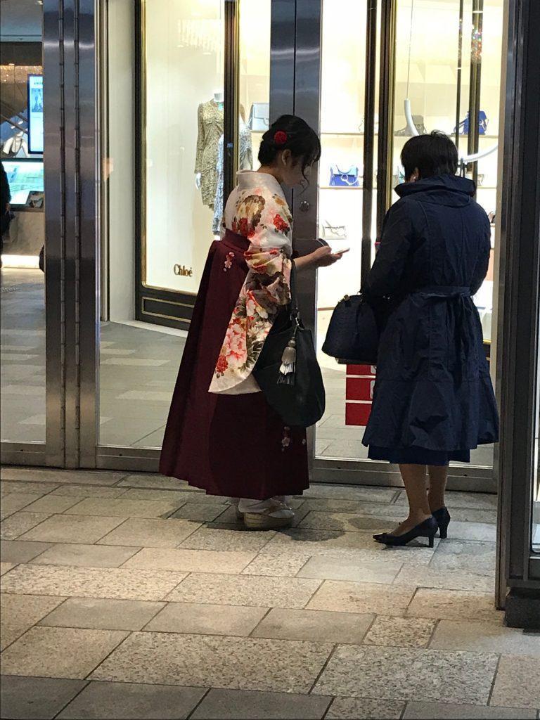 Dwie kobiety przed centrum handlowy w Tokio. Młodsza jest tradycyjnie ubrana w kimono, starsza w zachodnie, eleganckie ubrania. Japonia 2018. Zdjęcie autorki.