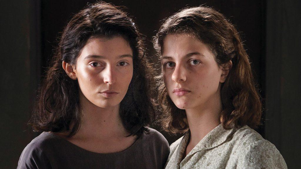 Dwie młode kobiety, jedna brunetka a druga blondynka wpatrują się w widza.