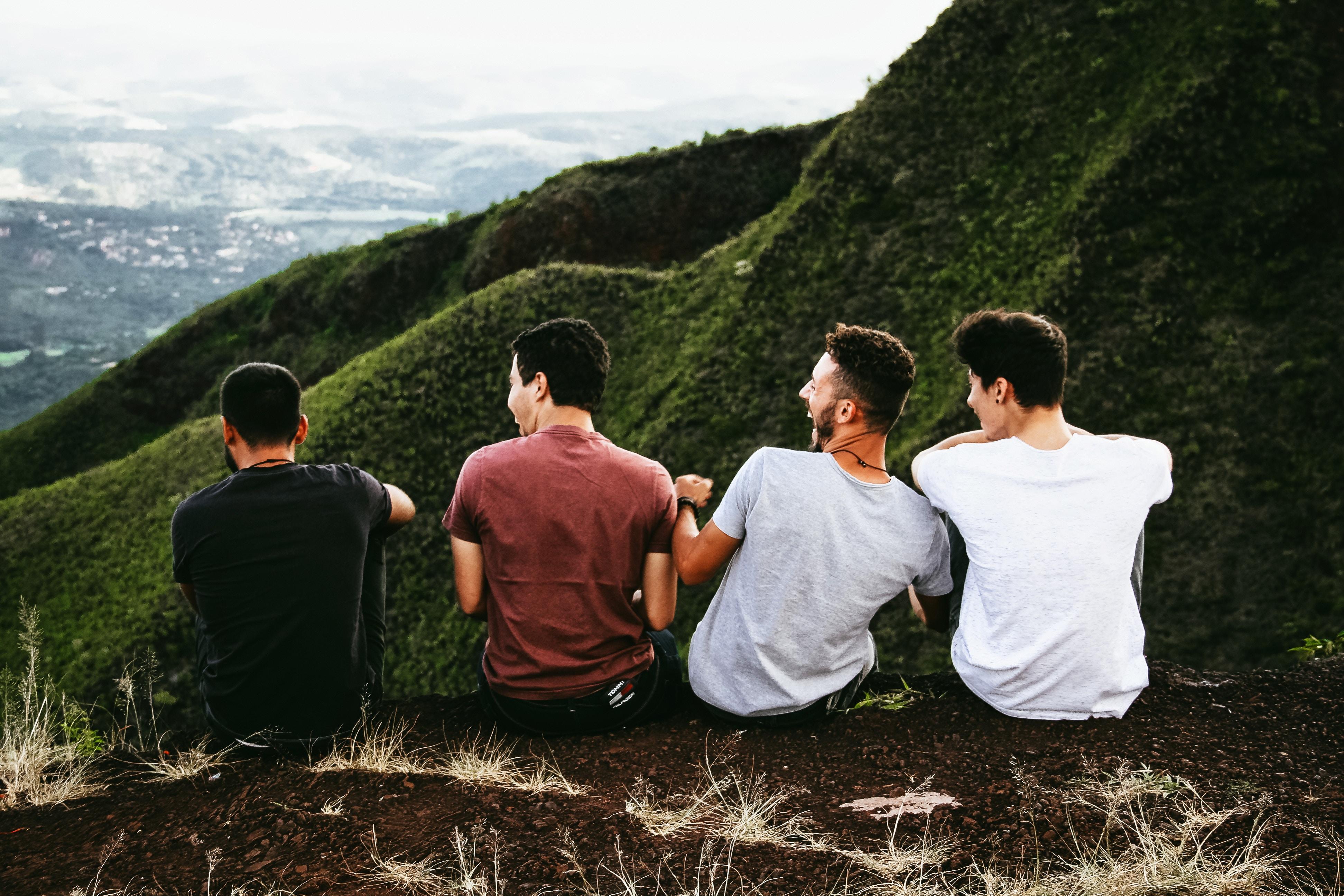Czterech młodych mężczyzn siedzi na skraju zbocza, widać, że dobrze się bawią i są zrelaksowani.
