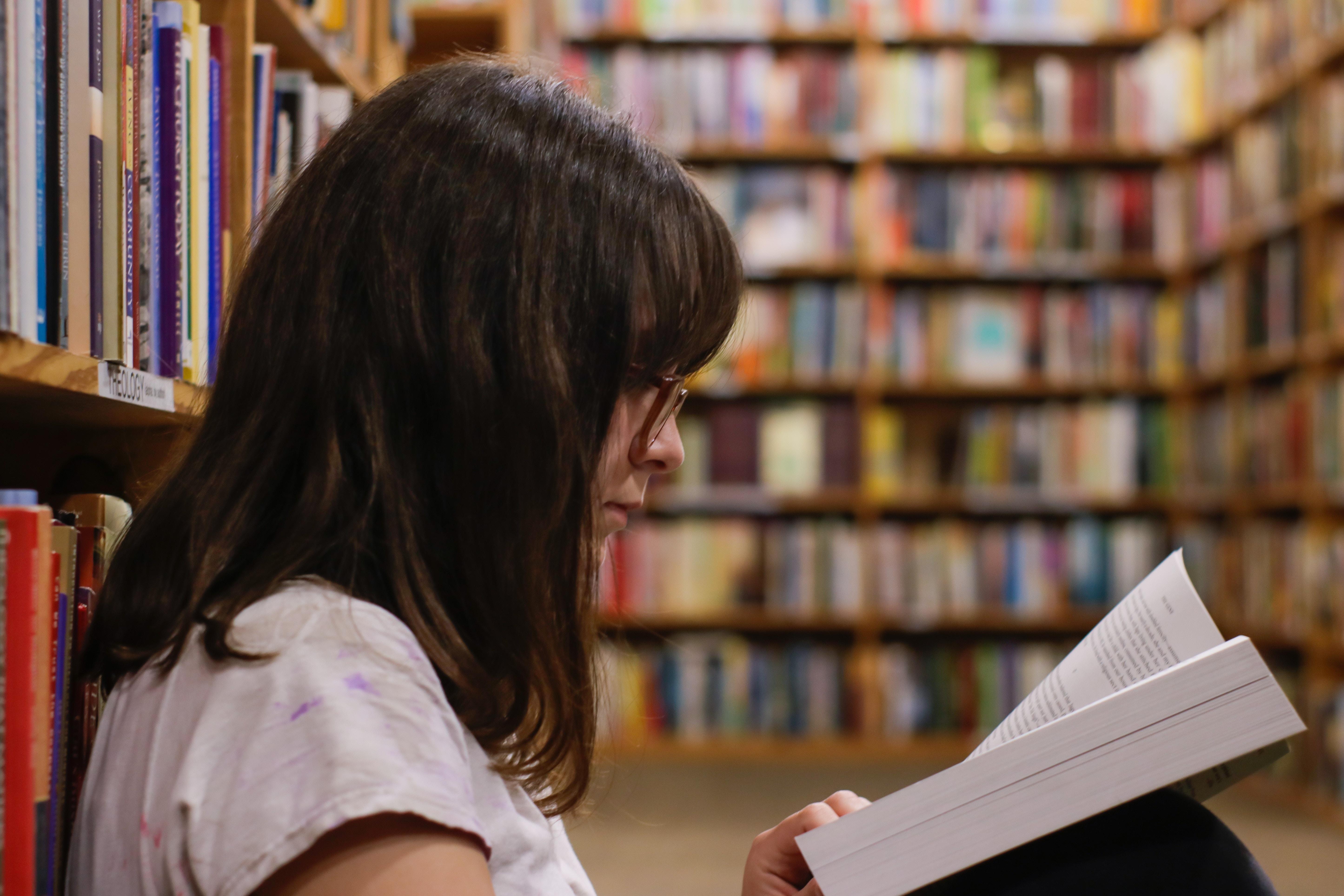 Na zdjęciu kobieta siedzi oparta o regał z książkami i czyta książkę w bibliotece